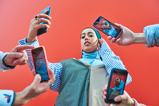 Young woman having picture taken by multiple smartphones. - gettyimageskorea