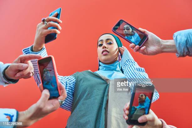 young woman having picture taken by multiple smartphones. - hi tech moda stock pictures, royalty-free photos & images