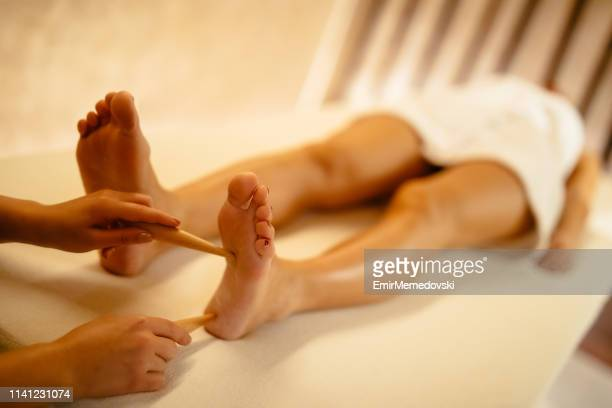 young woman having relaxing foot massage in beauty salon - foot massage stock pictures, royalty-free photos & images