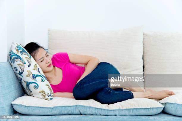 Young woman having stomachache on sofa