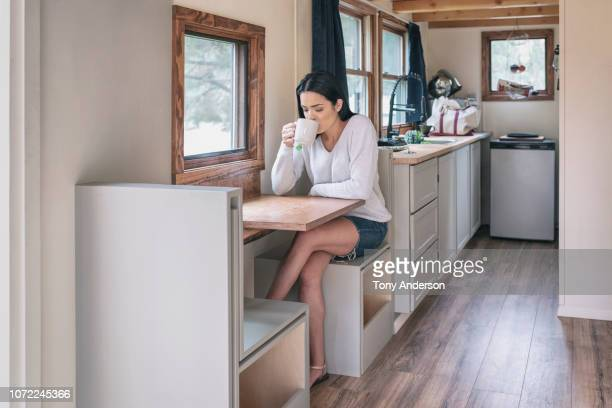 young woman having tea in her tiny house - wohngebäude innenansicht stock-fotos und bilder