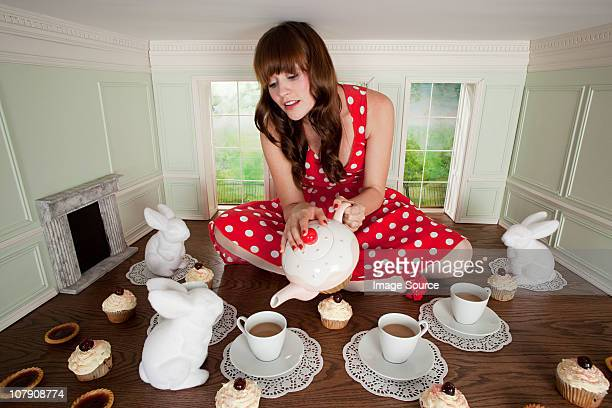 Young woman having tea party in small room