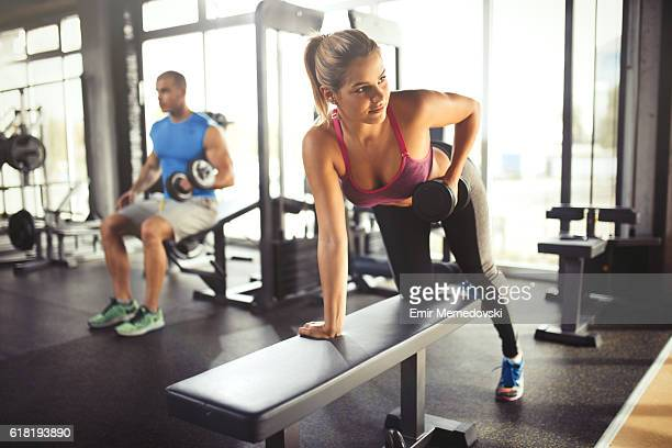 Young woman having weight training with dumbbells at gym .