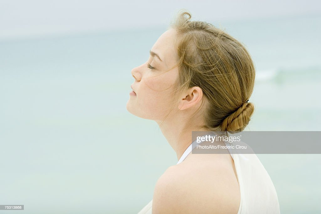 Young woman, head and shoulders, side view, sea in background : Stock Photo
