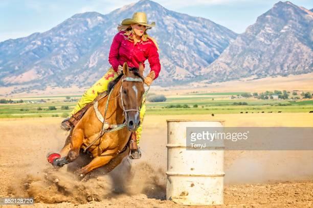 Mujer joven dirige su caballo alrededor de un barril durante una competencia de carreras de barril