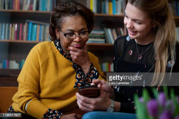 young woman helping a mature woman with her smartphone - lucy lambriex stockfoto's en -beelden