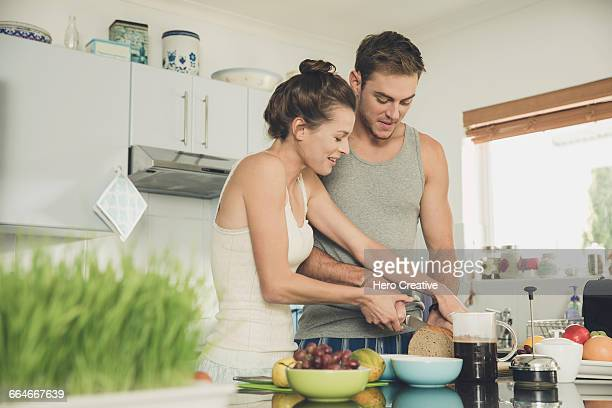 Young woman helping boyfriend to slice wholemeal bread at kitchen counter