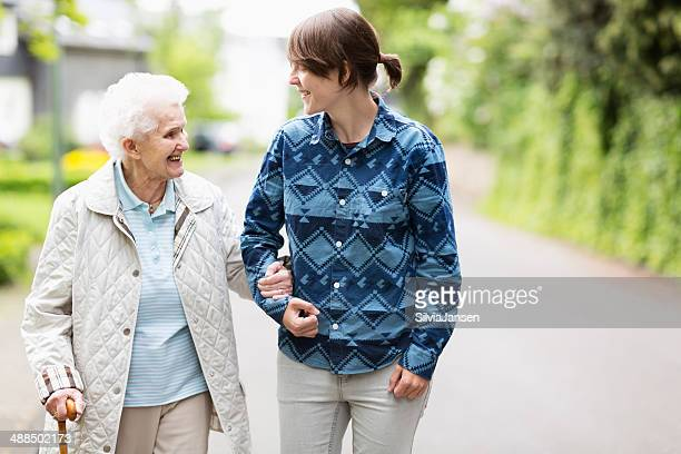 Young woman helping elderly woman walk down street