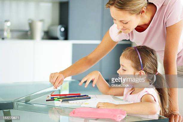 Young woman helping her daughter in drawing