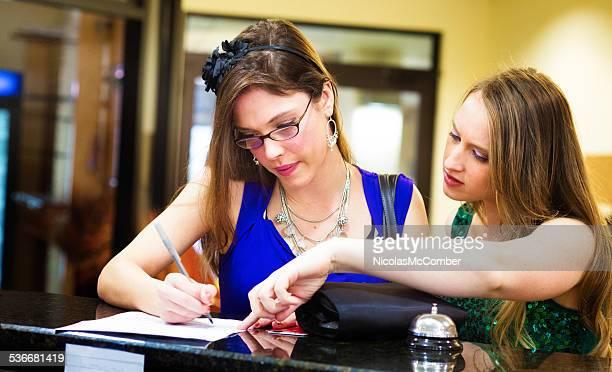 Jovem mulher ajudando seu amigo registo no hotel