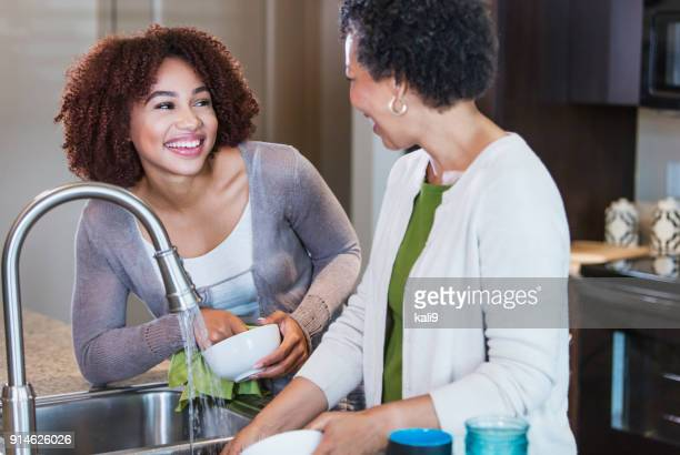 Young woman helping mother wash the dishes