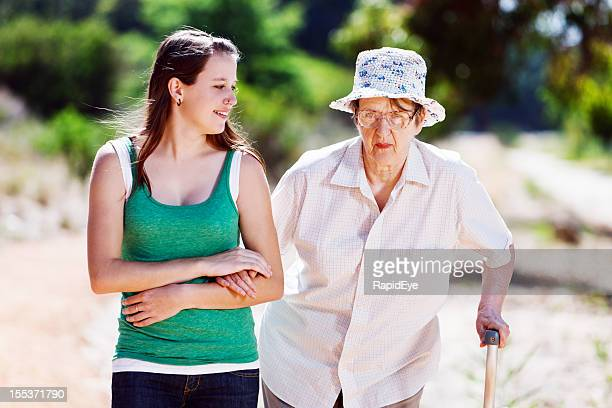 Young woman helping old lady with stick to walk