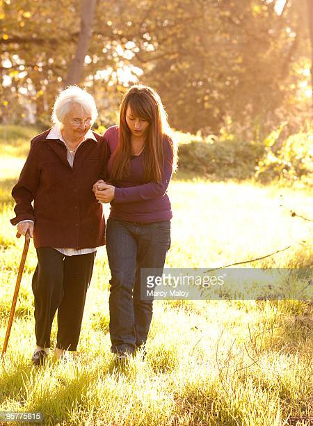young woman helping older women walk in woods - doing a favor stock pictures, royalty-free photos & images