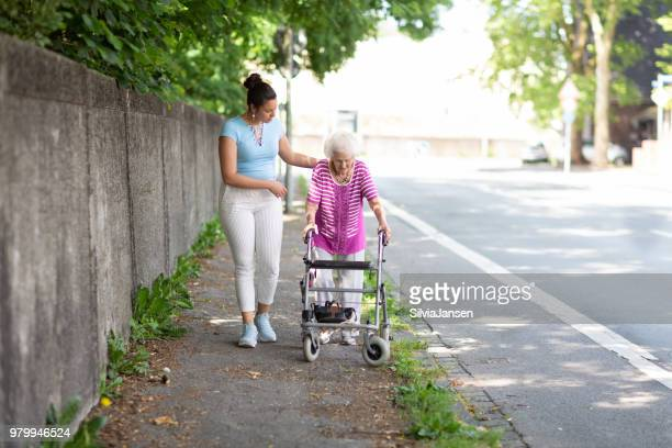 young woman helping senior woman walking in the street - a helping hand stock pictures, royalty-free photos & images