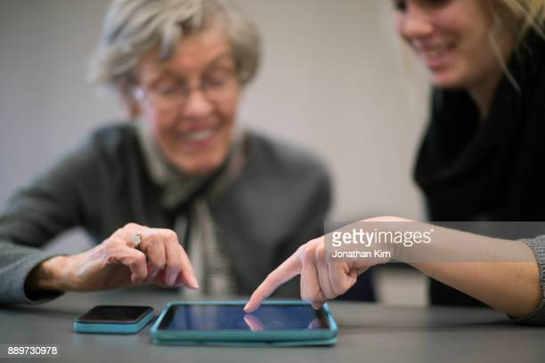 Young woman helps senior adult with tech devices.