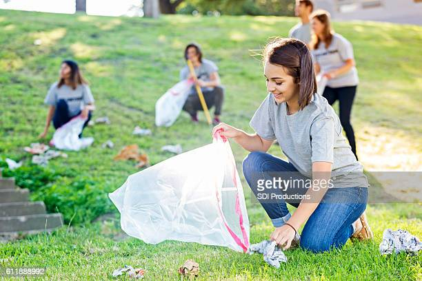 young woman helps with community clean up - 持ち上げる ストックフォトと画像