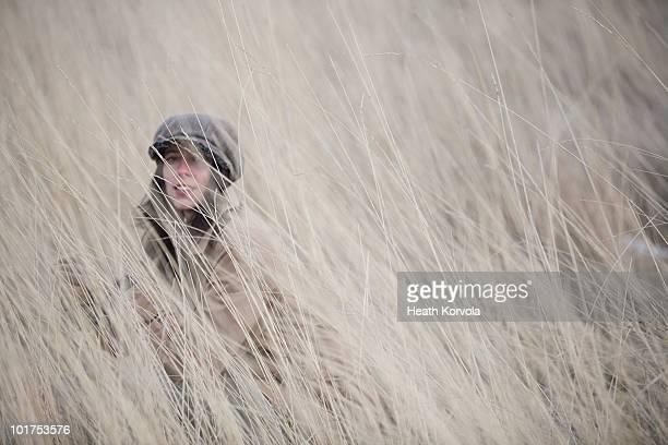 young woman hides in field of winter grass. - boina masculina - fotografias e filmes do acervo