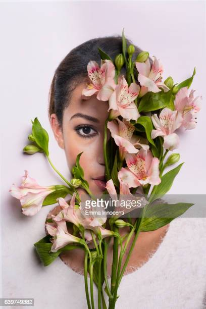 Young woman hiding behind flowers