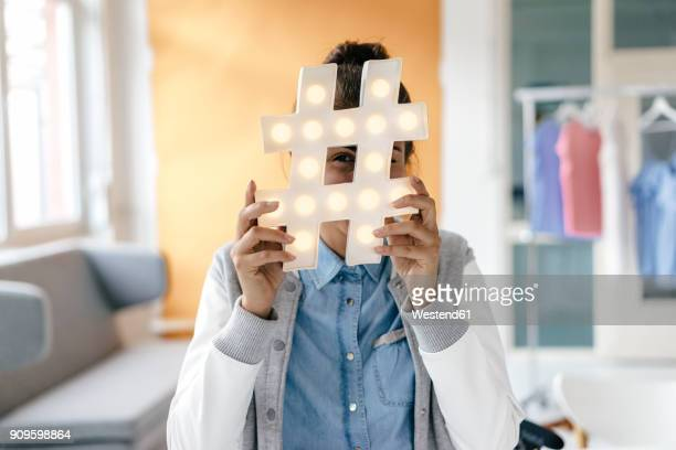 young woman hiding behind hashtag sign in studio - influencer stock pictures, royalty-free photos & images