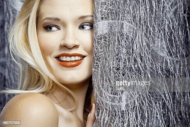Young woman hiding behind silver curtain