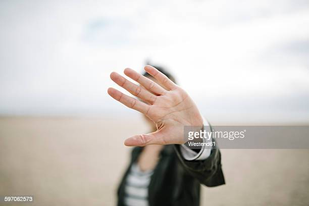 Young woman hiding face behind her outstretched hand