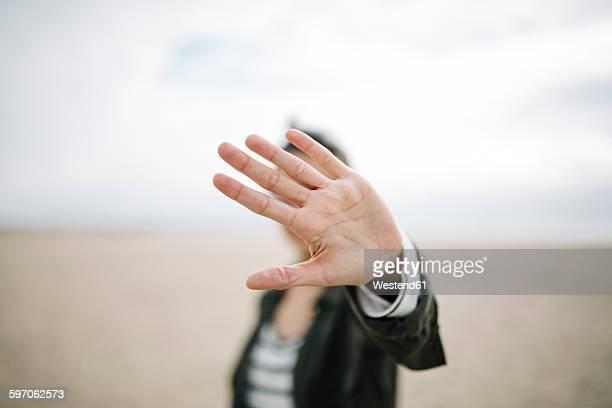 young woman hiding face behind her outstretched hand - rosto coberto - fotografias e filmes do acervo
