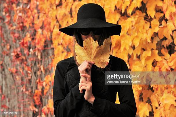 Young Woman Hiding Face With Autumn Leaf