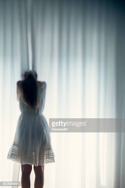 Young woman hiding her face behind a white curtain, back view
