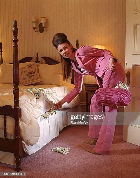 Young woman hiding money under mattress