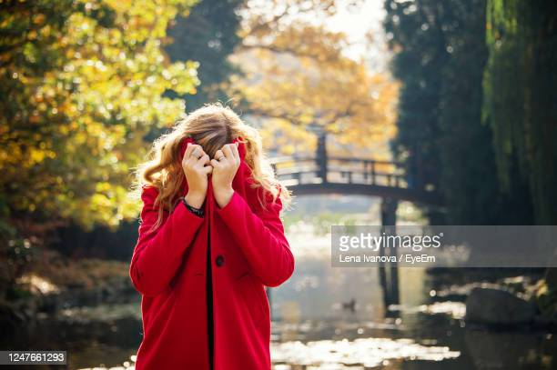 young woman hiding under red coat in autumn city park near lake - lena spoof stock pictures, royalty-free photos & images