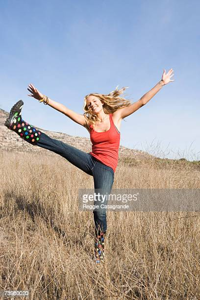Young woman high-kicking in grassland, smiling, portrait