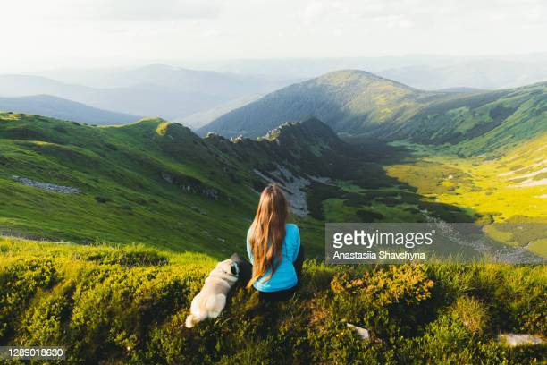 young woman hiker enjoying the mountain view with her dog from the top - ukraine landscape stock pictures, royalty-free photos & images