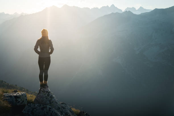 Young Woman Hiker Standing On The Edge Of Cliff At Sunrise. Backlight Sunlight  Sunbeam. Copy Space