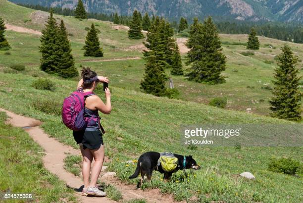 Young Woman Hiker Taking a Picture With Her Smart Phone