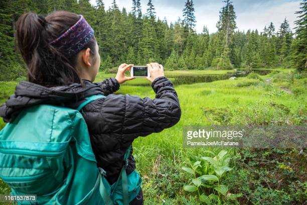 young woman hiker taking photo of alpine lake with smartphone - photo messaging stock pictures, royalty-free photos & images