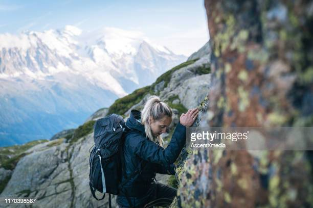 young woman hikes through alpine boulders - navy blue stock pictures, royalty-free photos & images