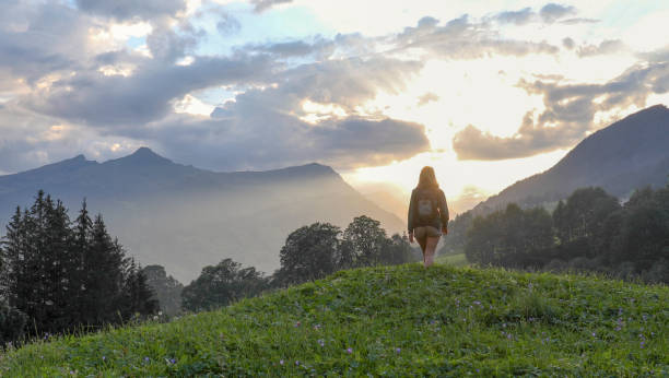 Young woman hikes to the top of a grassy knoll in the mountains