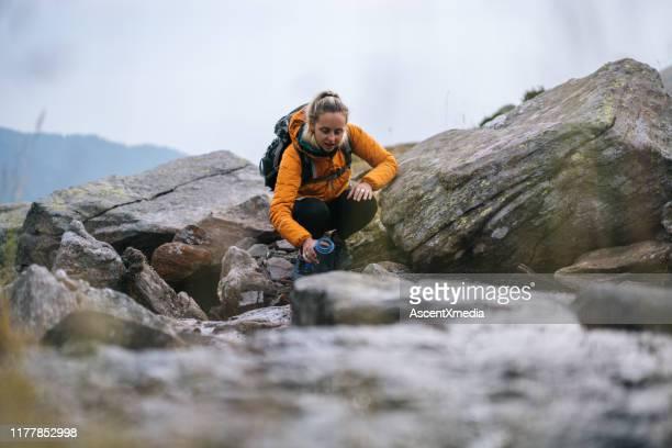 junge frau wandert einen felsigen hang in den bergen hinauf - einfaches leben stock-fotos und bilder