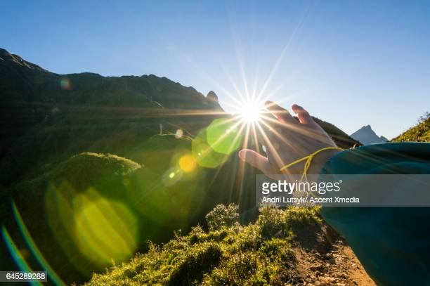 Young woman hikes up mountain slope, sunrise