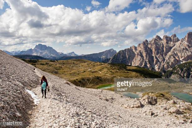 young woman hiking along rocky terrain with beautiful panorama view to the mountain - ecoturismo foto e immagini stock