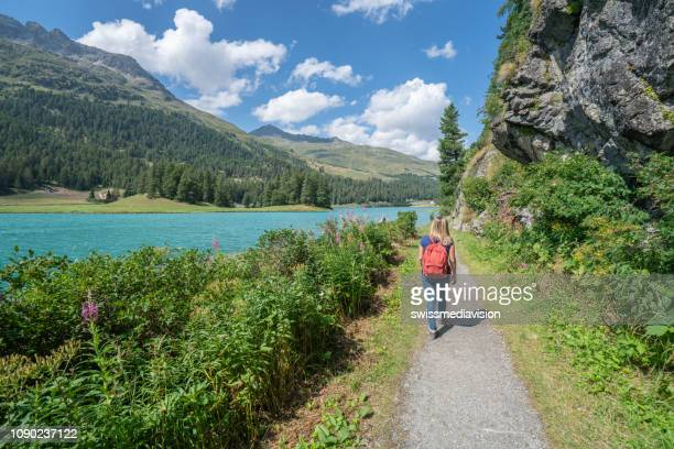 young woman hiking and walking near mountain lake - lakeshore stock pictures, royalty-free photos & images