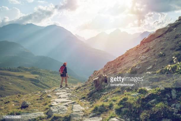 junge frau wandert und wandert auf bergweg am sonnenuntergang-schweiz - tal stock-fotos und bilder