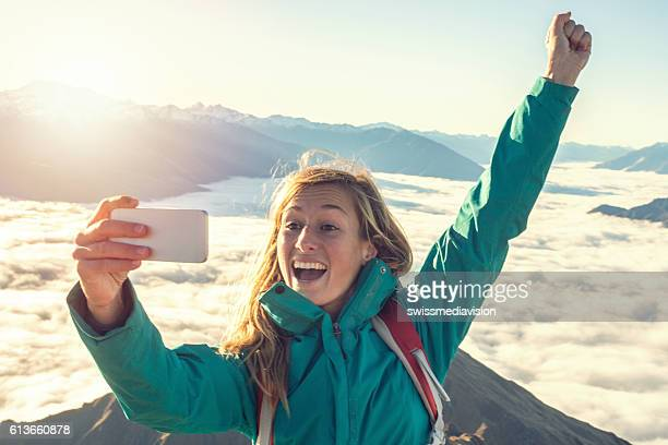 Young woman hiking captures successful moment with selfie