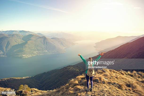 Young woman hiking celebrates at mountain top