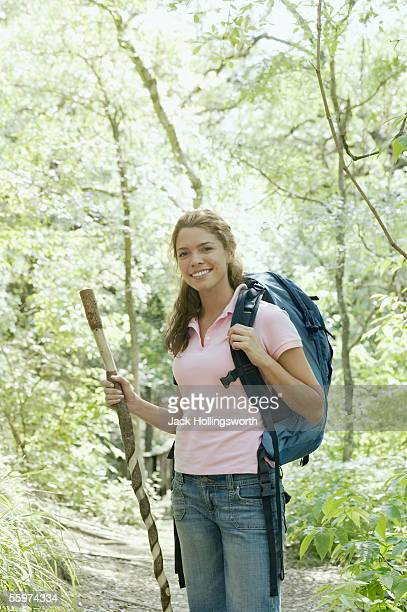young woman hiking in a forest - stick stock-fotos und bilder