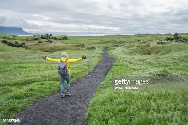 Young woman hiking in Iceland arms outstretched for freedom, rear view of person, Springtime overcast sky
