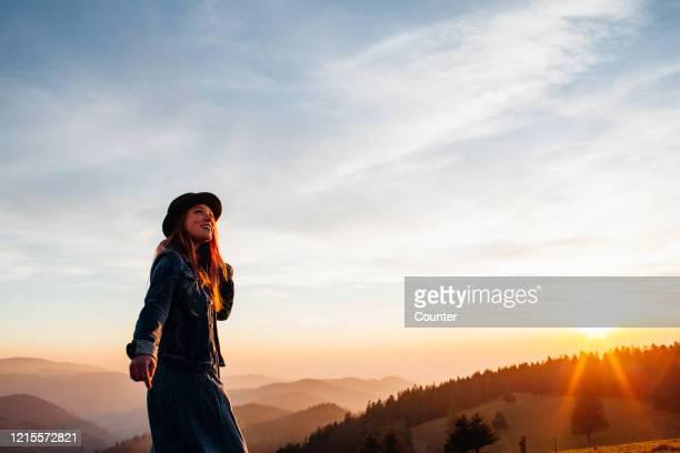 young woman hiking in mountains at sunset, smiling - freizeitaktivität im freien stock-fotos und bilder