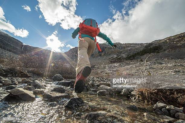Young woman hiking jumps over the mountain river