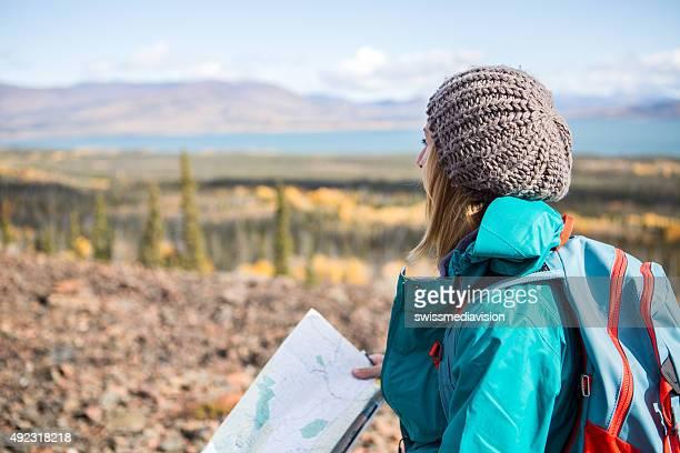 Jeune femme hiking looks pour obtenir des indications sur la carte
