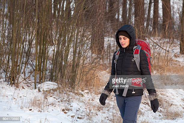 young woman hiking on snowy footpath - religious celebration stock pictures, royalty-free photos & images